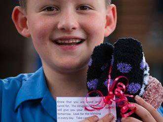 Suncoast Primary student wrapping winter woolly gifts for the homeless